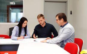 monitoring kosztów - trzy osoby dyskutujące przy stole